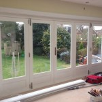 Double glazed hardwood bi-fold doors painted white